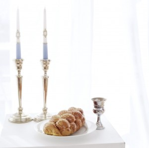 Table with Silver Candle Stands Beside Wine Chalice and Loaf of Bread